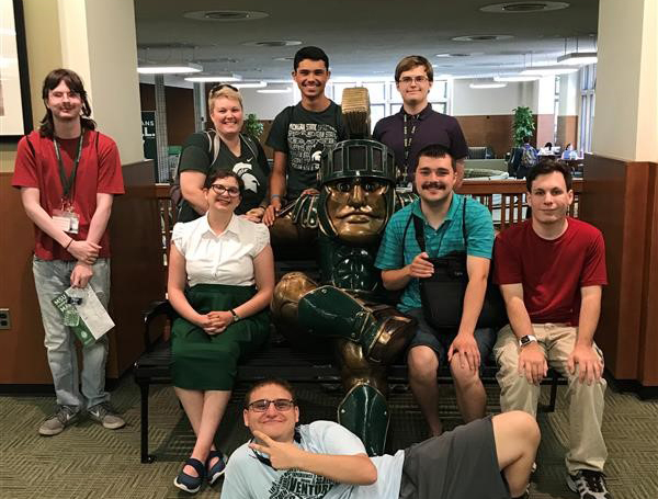 Photo of BOND early move-in group posting with a statue of Sparty