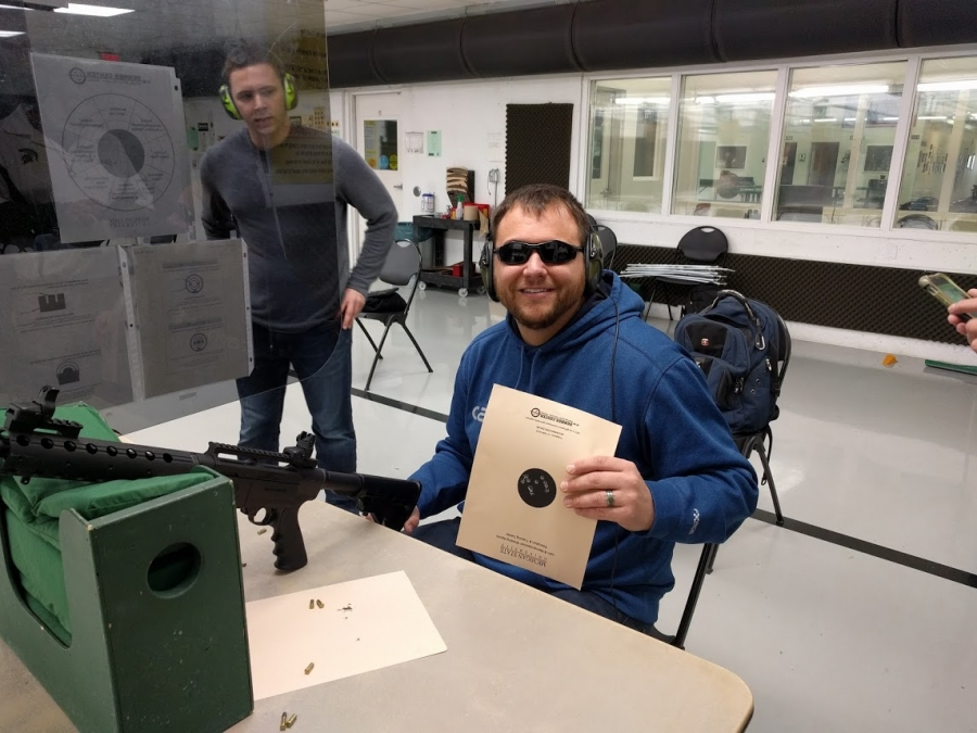 Nick V., person with visual impairment, poses with shooting target.