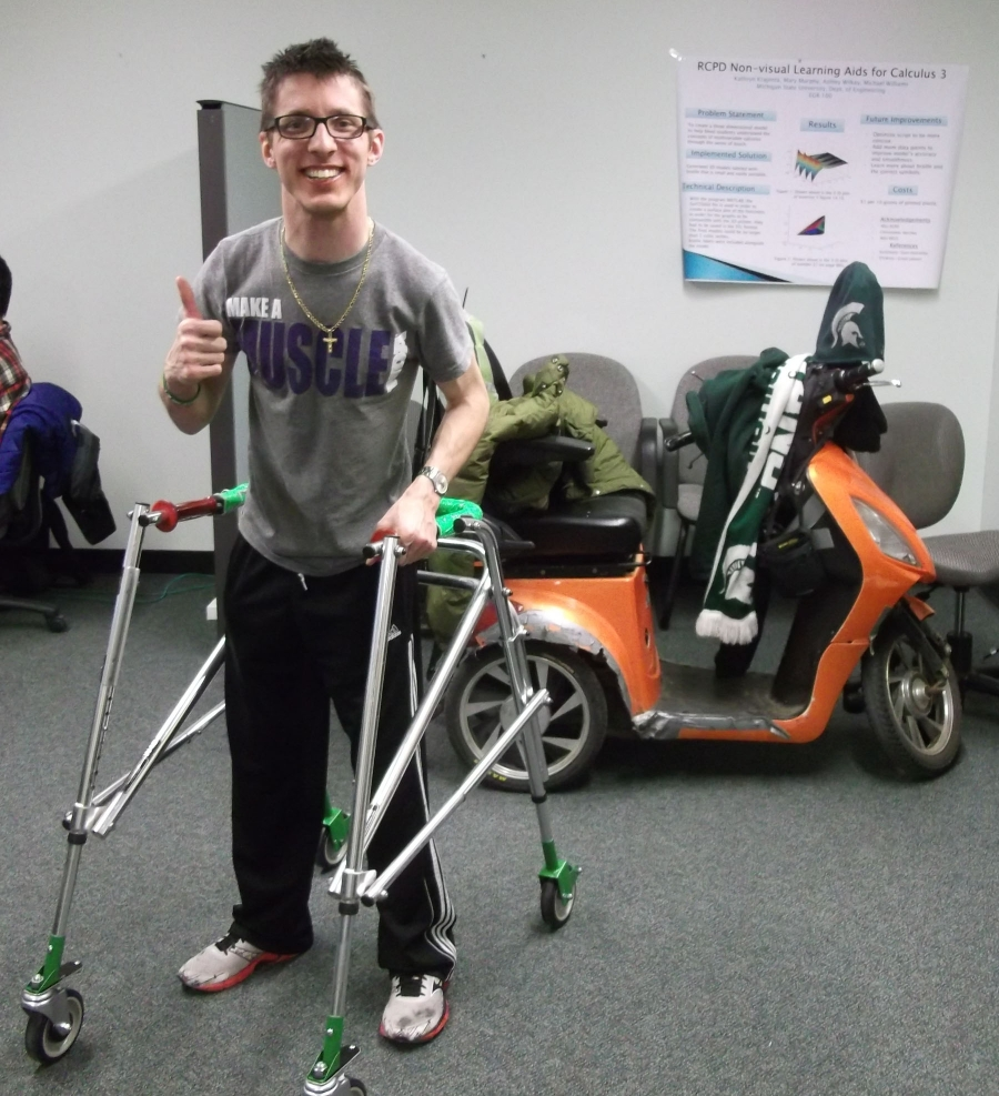 Student standing with athletic walker, smiling and giving a thumbs up.