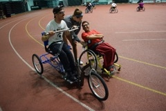 Members of the MSU Adaptive Sports Club test out the new adaptive cycle at their regular club gathering.