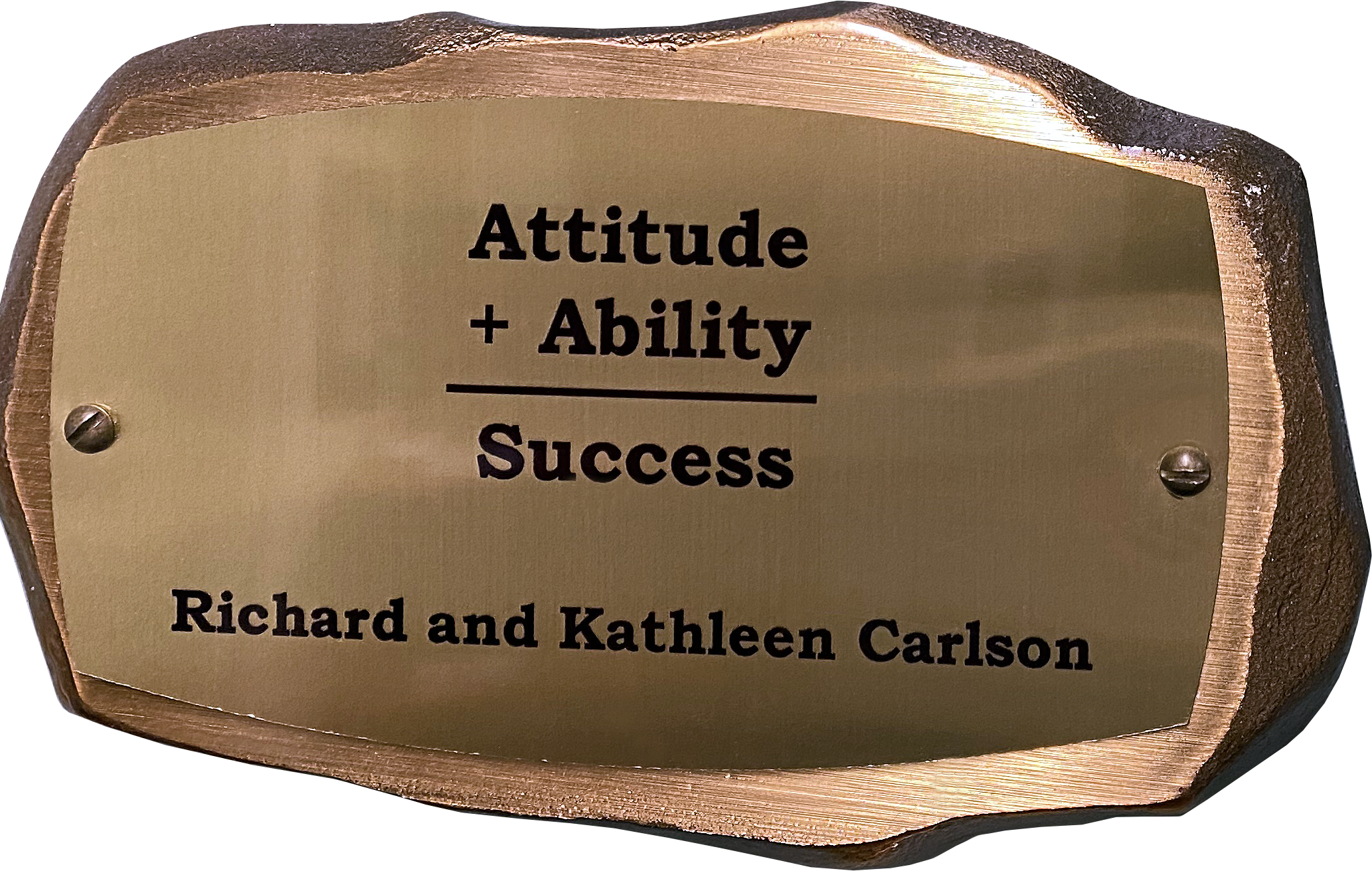 Inscribed bronze plaque in the shape of a rock with text on it reading: Attitude + Ability = Success. Richard and Kathleen Carlson