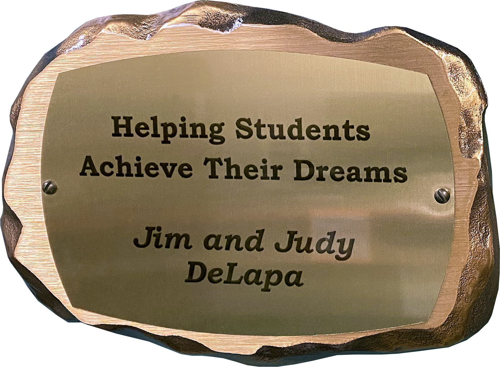 Inscribed bronze plaque in the shape of a rock with text on it reading: Helping Students Achieve Their Dreams. Jim and Judy DeLapa