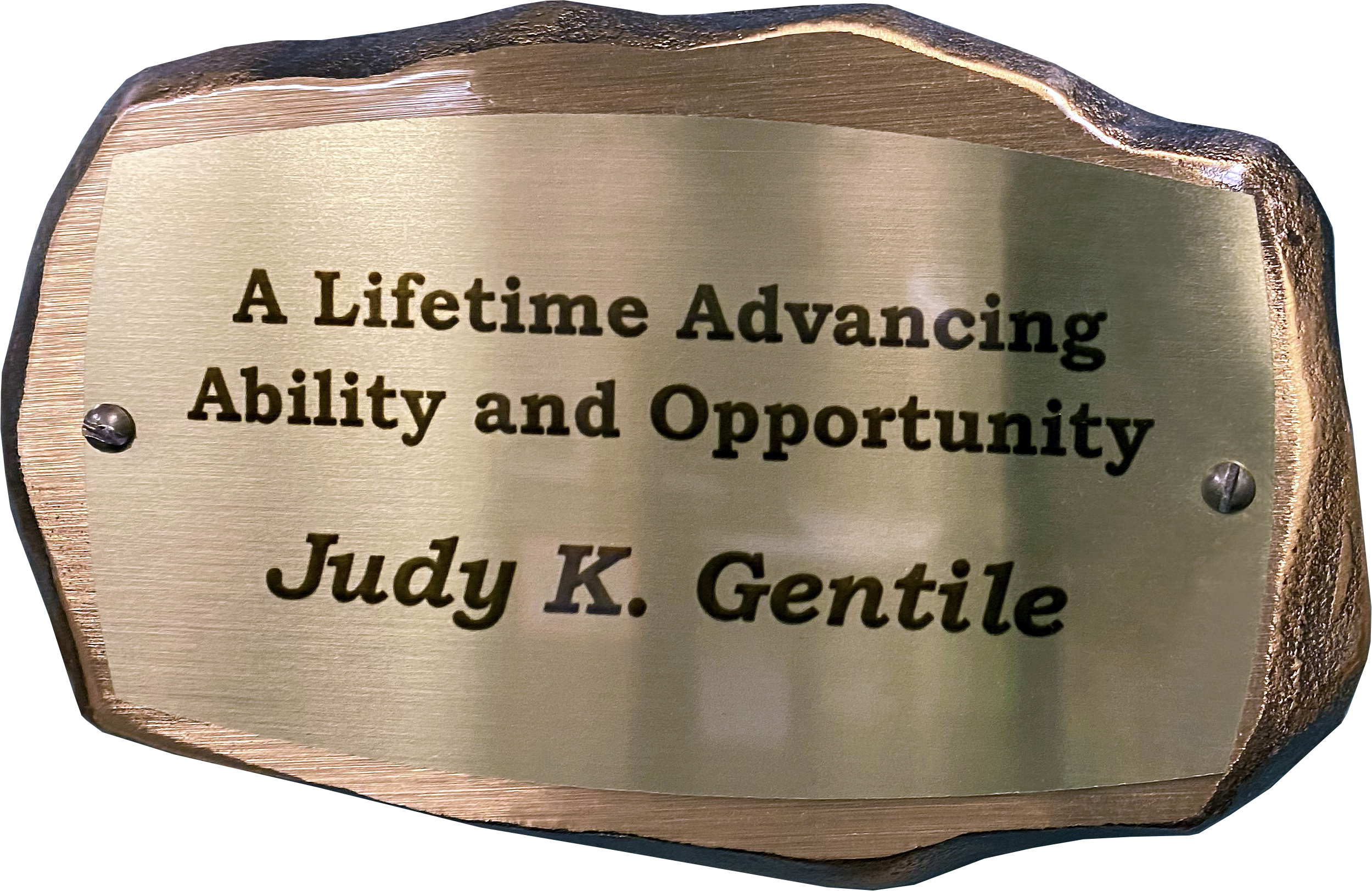 Inscribed bronze plaque in the shape of a rock with text on it reading: A Lifetime Advancing Ability and Opportunity. Judy K. Gentile