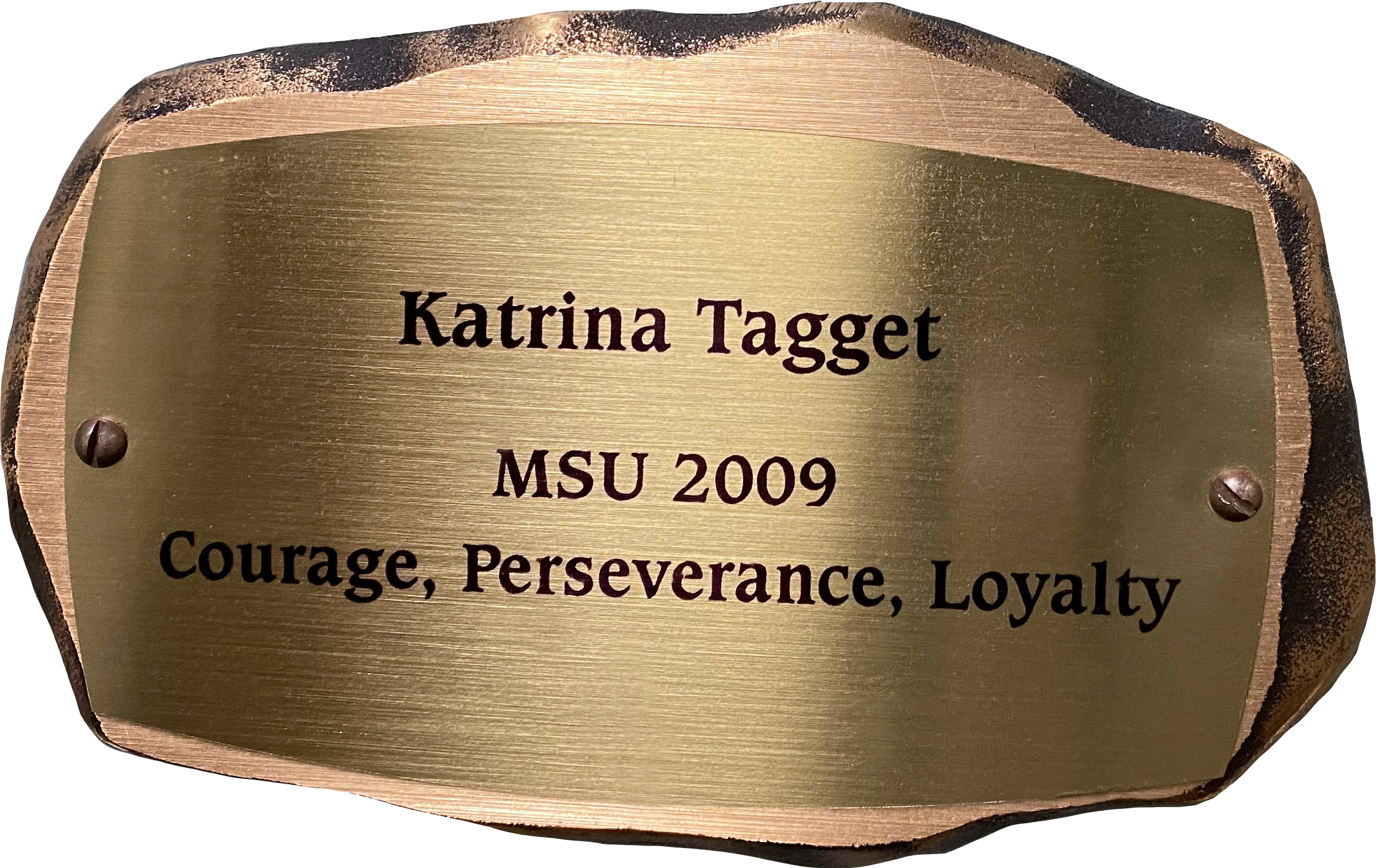 "Inscribed bronze plaque in the shape of a rock with text on it reading: ""Katrina Tagget MSU 2009 Courage, Perseverance, Loyalty"""