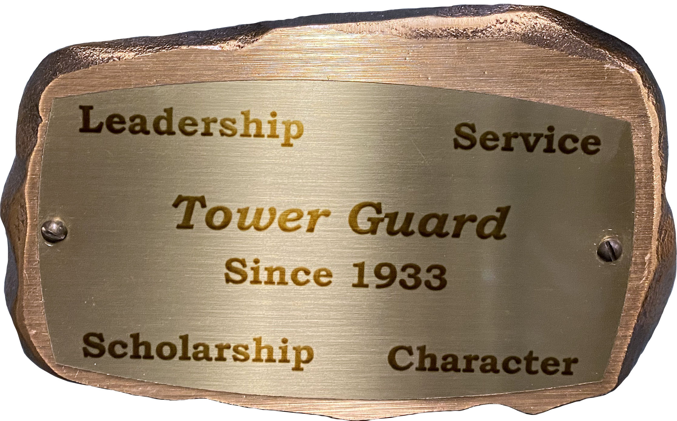 "Inscribed bronze plaque in the shape of a rock with text on it reading: ""Leadership, Service, Tower Guard, Since 1933, Scholarship, Character"""