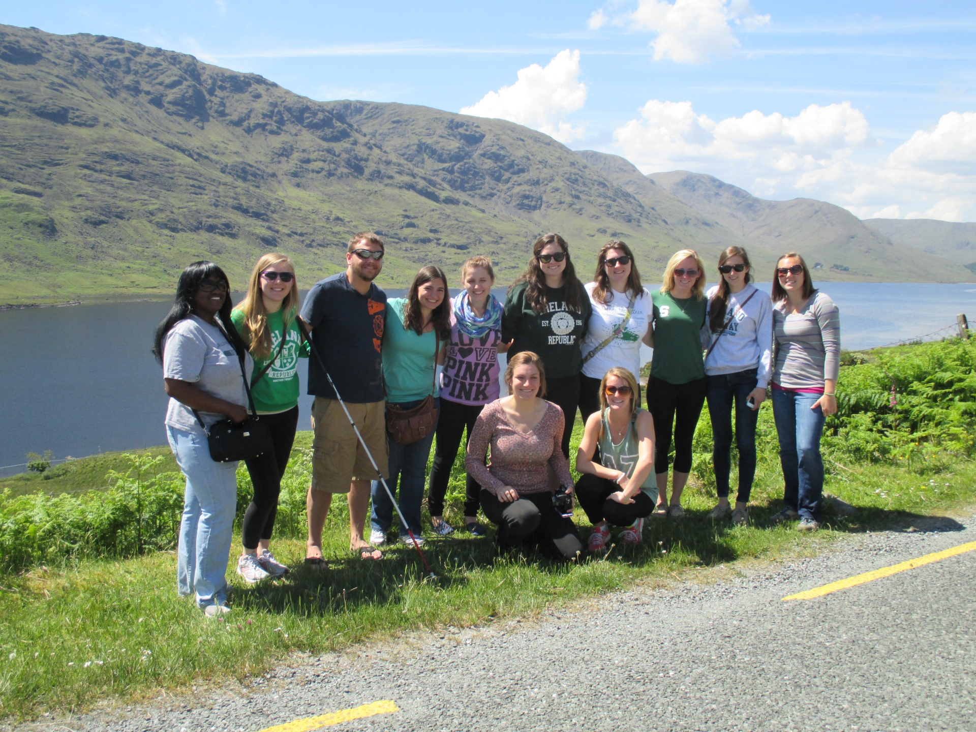 Study abroad students standing roadside in front of a lake and green mountain range