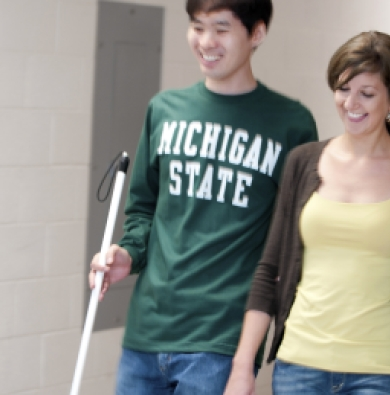 Two students walking together, one wearing a yellow shirt with a brown cardigan, and one wearing an MSU shirt and carrying a white cane.